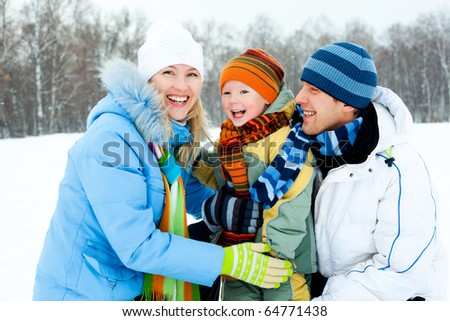 happy young family spending time outdoor on a winter day - stock photo