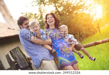 Happy young family spending time together and having fun in front of an old countryside house. - stock photo