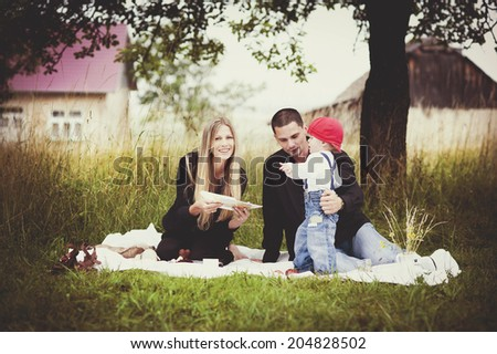 Happy young family spending time together in green nature. - stock photo