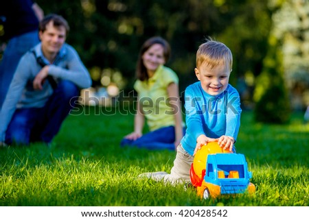 Happy young family stands near a flowering tree and smiling. Spring