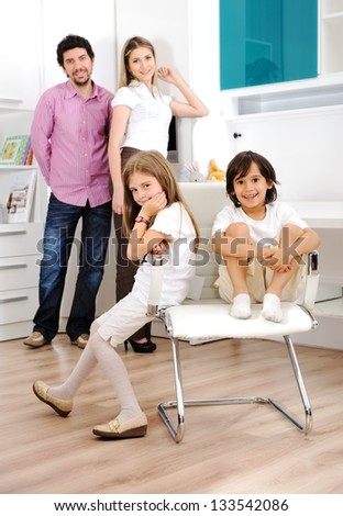 Happy young family together at home posing for portrait - stock photo