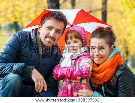 Happy young family under an umbrella in an autumn park - stock photo