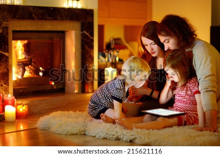 Happy young family using a tablet pc at home by a fireplace in warm and cozy living room on winter day - stock photo