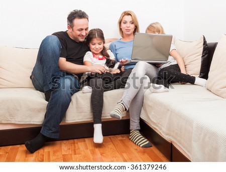 Happy young family using laptop on the couch or sofa in the living room