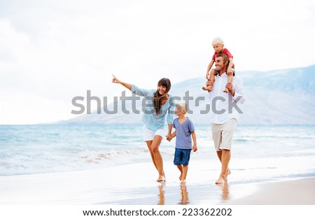 Happy Young Family Walking Down the Beach at Sunset - stock photo