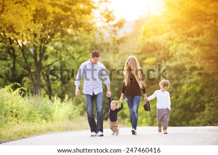 Happy young family walking down the road outside in green nature. - stock photo