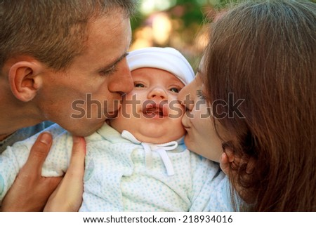 Happy young family with baby in the park. Parents kissing their child - stock photo