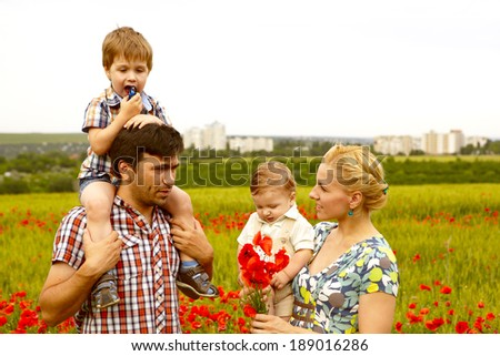 Happy young family with children resting outdoors in poppies field