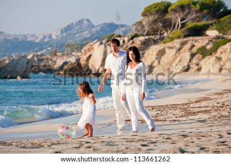 happy young family with daughter on beach in summer lifestyle - stock photo