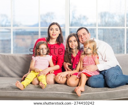 Happy young family with kids near the window at home - stock photo