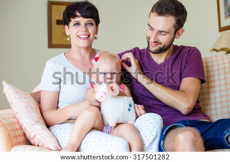 Happy young family with little child at home