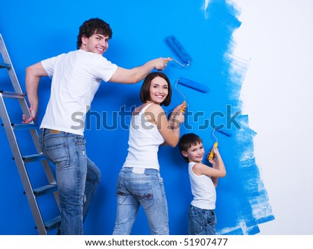 Happy young family with little son painting the wall - stock photo