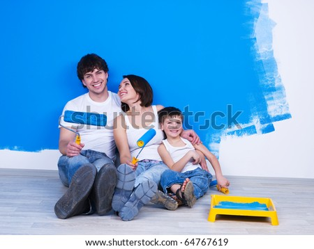 Happy young family with little son sitting near the wall with paintbrush - stock photo