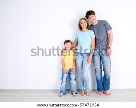 Happy young family with little son standing together in casuals near the empty wall - indoors - stock photo