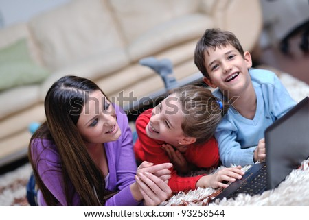 happy young family with mom and kids have fun and play in modern new living room home indoor - stock photo