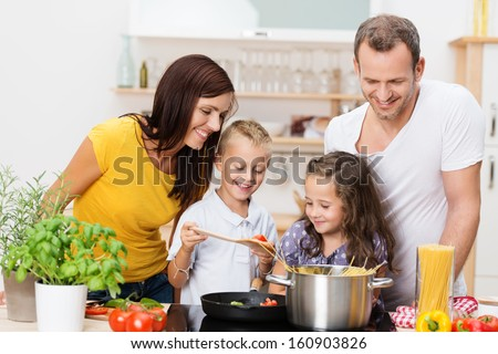 Happy young family with Mum, Dad and two young children cooking in the kitchen preparing a spaghetti meal together - stock photo