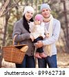 happy young family with their daughter having a picnic in the autumn park - stock photo