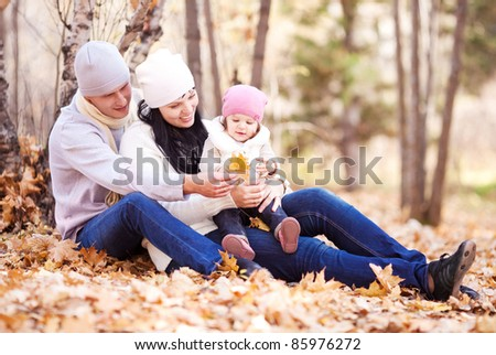 happy young family with their daughter spending time outdoor in the autumn park (focus on the woman)