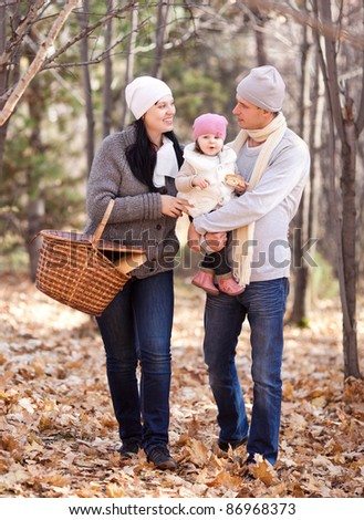 happy young family with their daughter spending time outdoor in the autumn park (focus on the woman) - stock photo