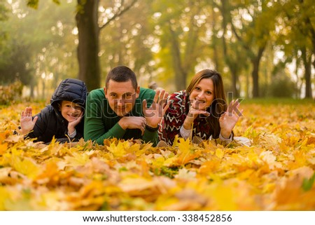 happy young family with their son spending time outdoor in the autumn park - stock photo