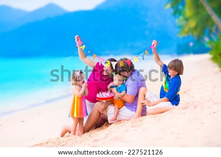 Happy young family with three children celebrating birthday party at a tropical beach. Parents with baby, teenager boy and cute little girl eating cake on summer vacation.