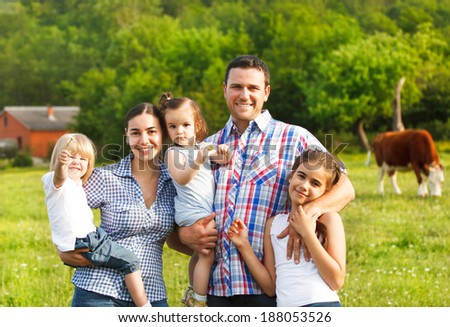 Happy young family with three children on the farm
