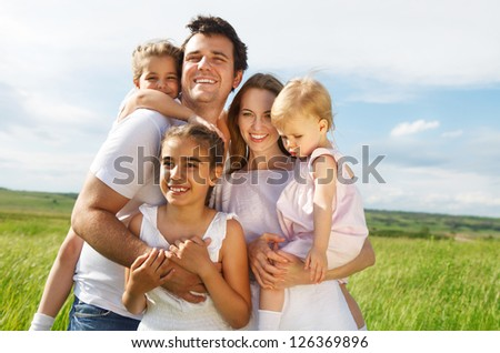 Happy young family with three children outdoors - stock photo