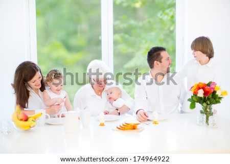 Happy young family with three children - teenager boy, cute toddler girl and a newborn baby - enjoying breakfast together with their grandmother in a sunny dining room with a big window - stock photo