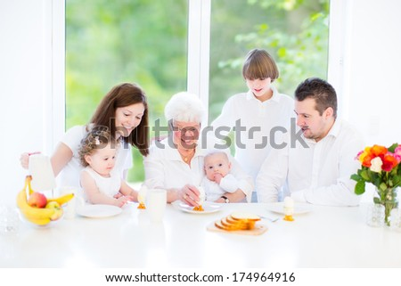 Happy young family with three children - teenager boy, toddler girl and a newborn baby - enjoying Easter breakfast with their grandmother in a sunny white dining room with a big window - stock photo