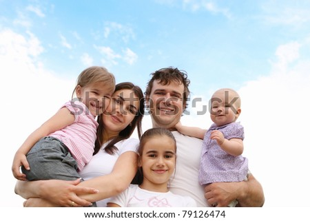 Happy young family with three daughters outdoors - stock photo