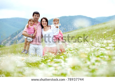 Happy young family with twins resting outdoors - stock photo