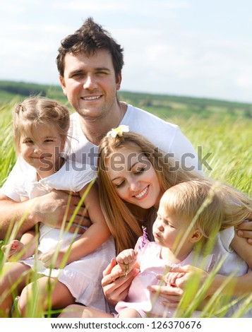 Happy young family with two children outdoors in summer day - stock photo