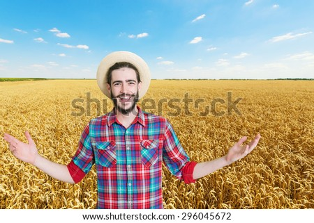 Happy, young farmer with arms outstretched in front of the golden wheat field - stock photo
