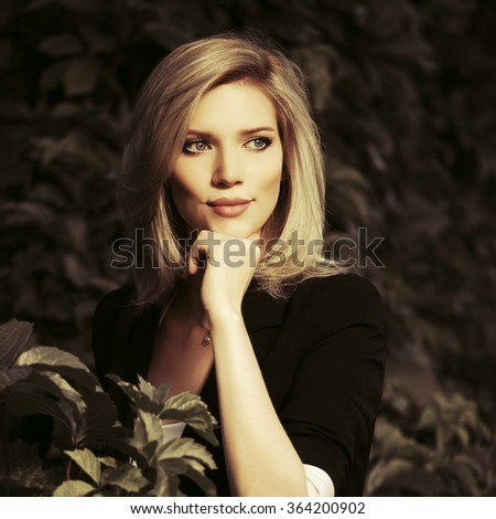 Happy young fashion business woman in a city park - stock photo