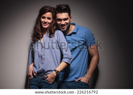 Happy young fashion couple posing embraced while holding their hands in pockets. - stock photo