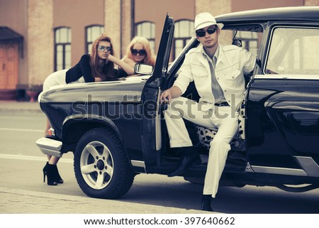 Happy young fashion man and women by retro car - stock photo