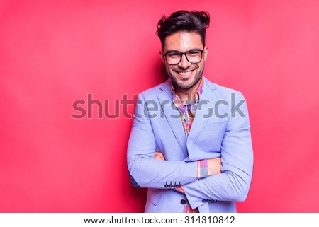 Happy young fashion man holdin his hands crossed, against a red wall. - stock photo