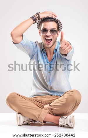 Happy young fashion man sitting with his legs crossed while holding one hand on his hat and showing thumbs up gesture with the other hand. - stock photo