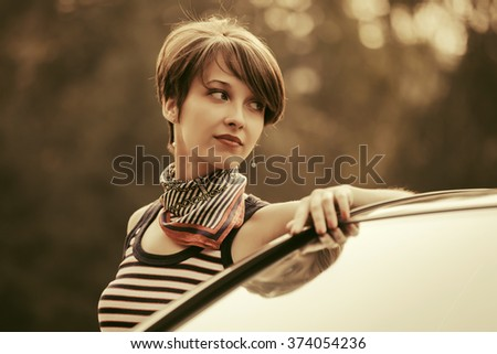 Happy young fashion woman by her car - stock photo