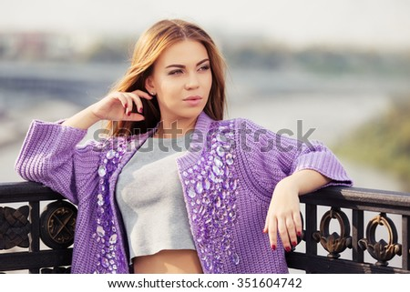 Happy young fashion woman daydreaming outdoor - stock photo