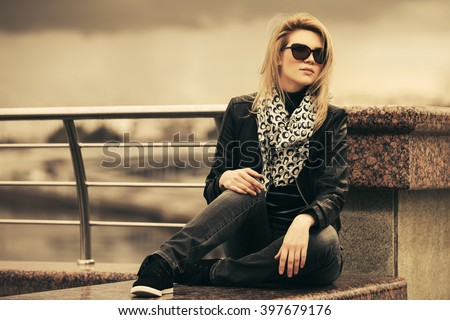 Happy young fashion woman in leather jacket outdoor - stock photo