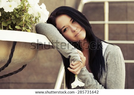 Happy young fashion woman with a flower daydreaming - stock photo