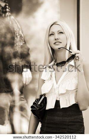 Happy young fashion woman with handbag at the mall window - stock photo