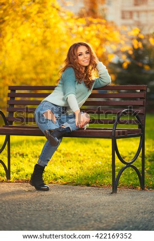 Happy young fashion woman with long curly hairs sitting on bench in city park - stock photo