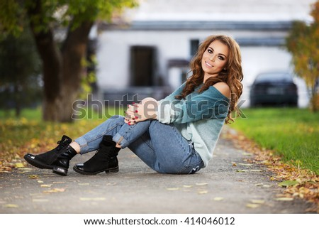 Happy young fashion woman with long curly hairs sitting on city street. Female fashion model outdoor - stock photo
