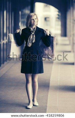 Happy young fashion woman with shopping bags in the mall. Female stylish model in black coat