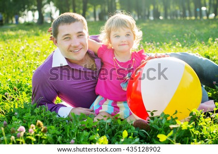 Happy young father and daughter on nature - stock photo