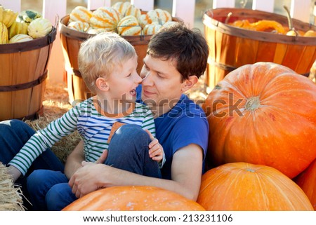 happy young father and his cute son spending fun time together at pumpkin patch; family of two at fall - stock photo