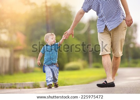 Happy young father holding his little son�s hand and walking on road - stock photo