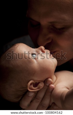 Happy Young Father Holding His Mixed Race Newborn Baby Under Dramatic Lighting. - stock photo